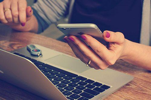 Tjej-surfar-på-mobilen-och-laptop